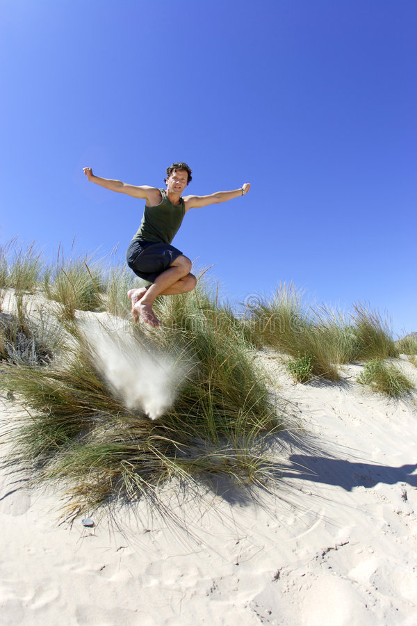 Fit, healthy middle aged man leaping over sand dunes royalty free stock photography