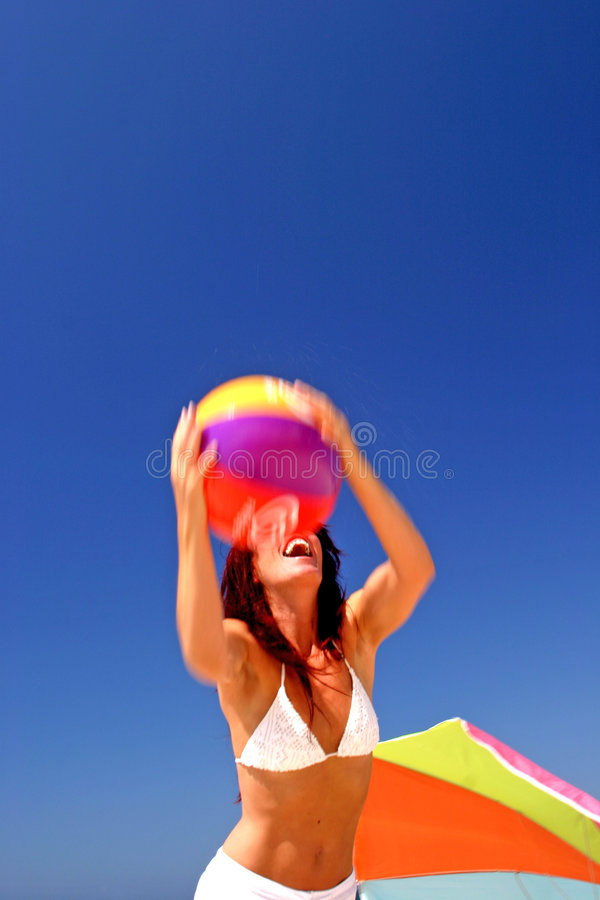 Fit and healthy woman catching beach ball on sunny beach in Spain. royalty free stock image