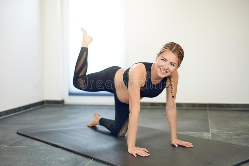 Fit healthy young pregnant woman exercising doing a yoga workout royalty free stock photography