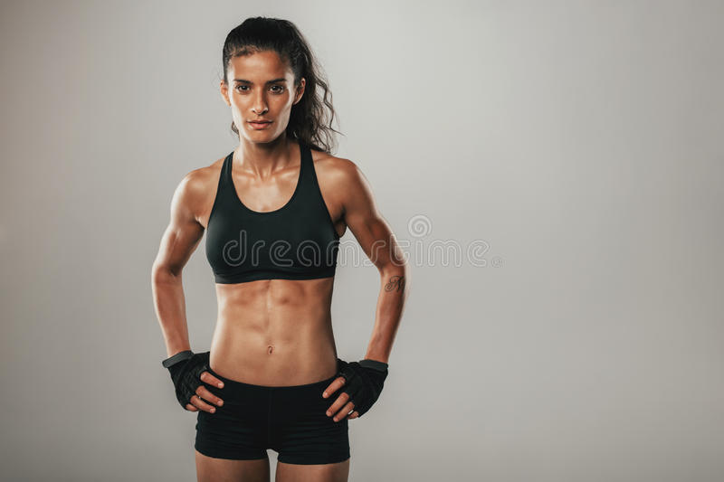 Fit healthy young woman with a toned physique. Standing looking seriously at the camera with her hands on her hips over grey with copy space royalty free stock photos