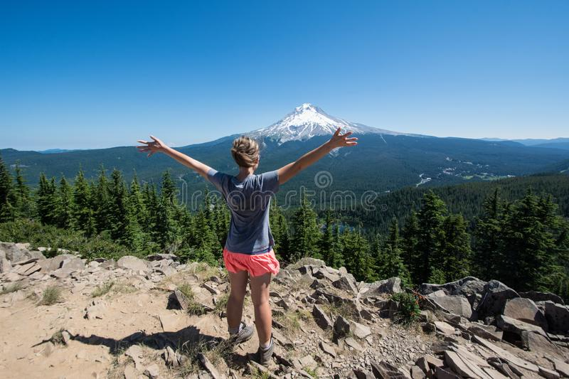 Female hiker stands on the summit of Tom and Harry Mountain in Mt. Hood National Forest, with her arms held up, looking at Mo. Fit hiker stands on the summit of royalty free stock photo