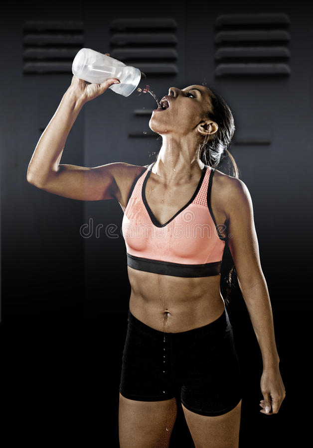 Fit latin sport woman in fitness clothes drinking water tired during training workout in healthy lifestyle. Young beautiful and fit latin sport woman in fitness stock photo