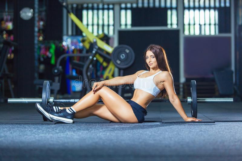Fit long-legged woman sitting on the floor at gym near barbell.  stock photography