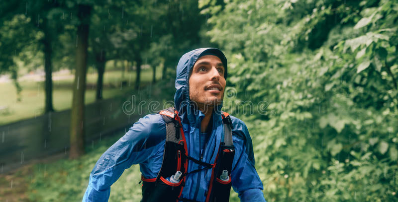 Fit male jogger day training in the rain for cross country forest trail race in a nature park. stock photo