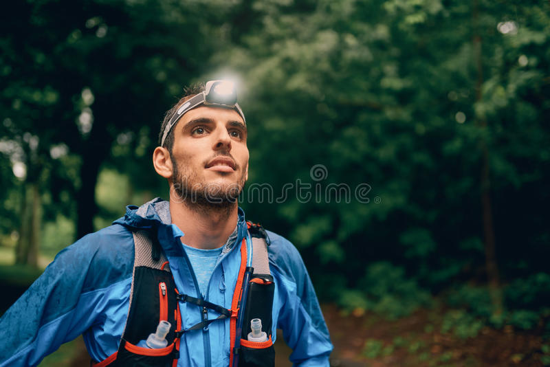 Fit male jogger with a headlamp rests during training for cross country trail race in nature park. royalty free stock images