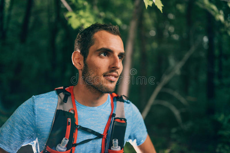 Fit male jogger resting during day training for cross country forest trail race in a nature park. royalty free stock photos