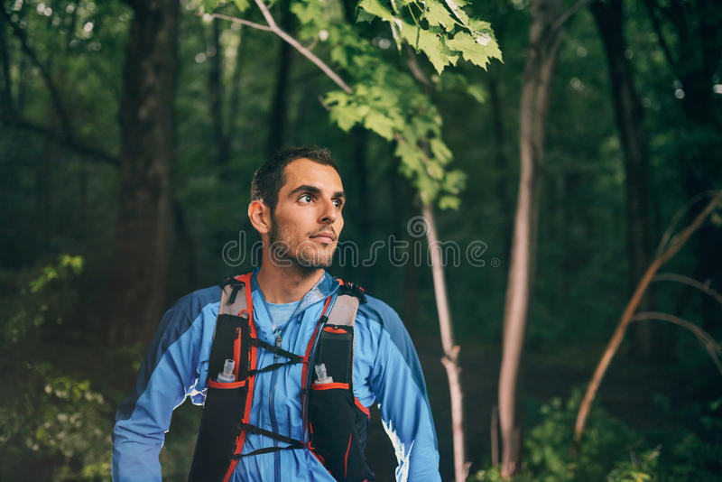 Fit male jogger resting during day training for cross country forest trail race in a nature park. stock photography