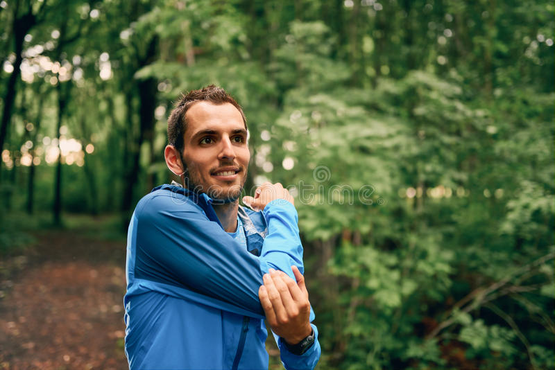 Fit male jogger stretches during day training for cross country forest trail race in a nature park. stock photo