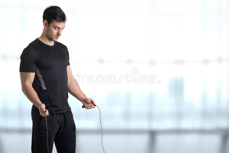 Fit Male Jumping Rope. Fit athlete jumping rope, in a gym royalty free stock image