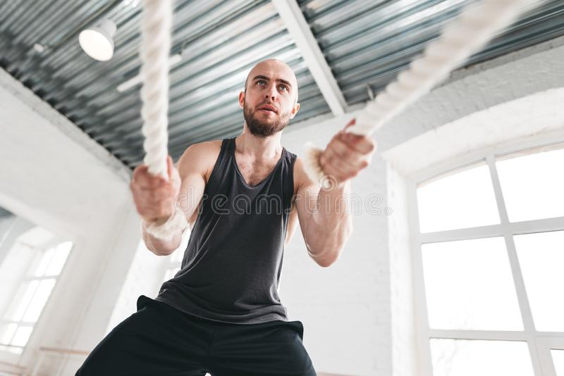 Strong fitness sportsman using training ropes for exercise at gym. Fit man athlete using battle ropes for exercising at light sport hall. Strong fitness stock image