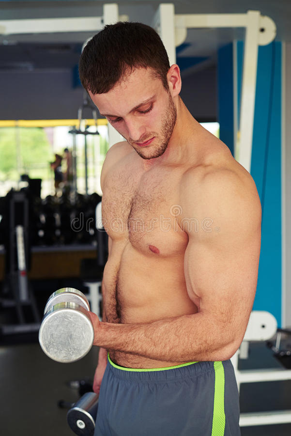 Fit man with bare chest is flexing biceps stock image