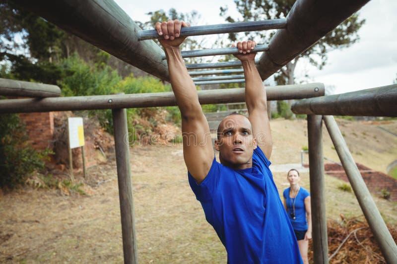 Fit man climbing monkey bars stock photos