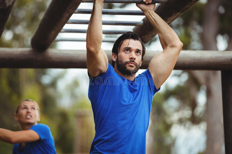 Fit man climbing monkey bars stock photo