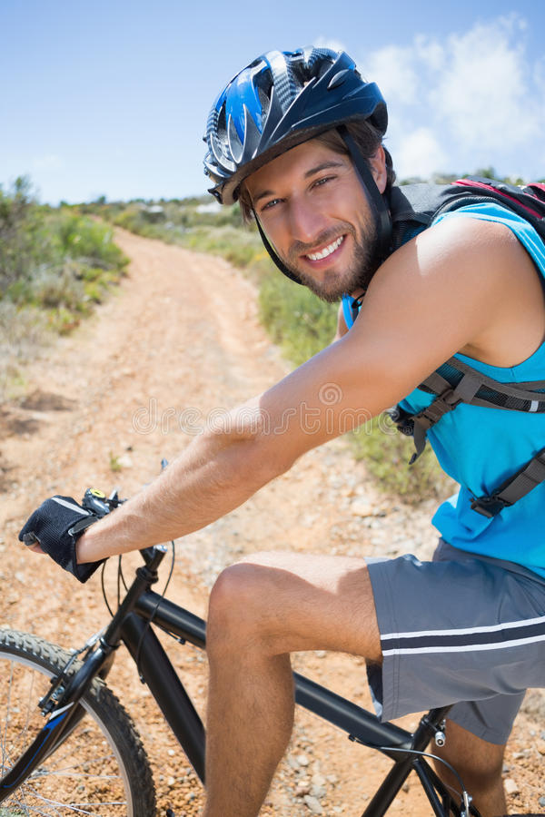 Fit man cycling up mountain trail smiling at camera. On a sunny day stock image