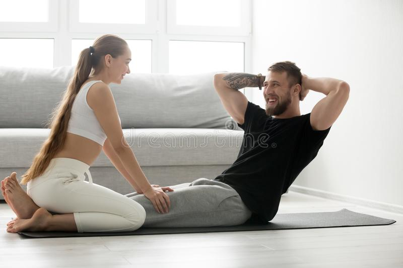 Fit man doing crunches exercise at home with girlfriends assista royalty free stock photography
