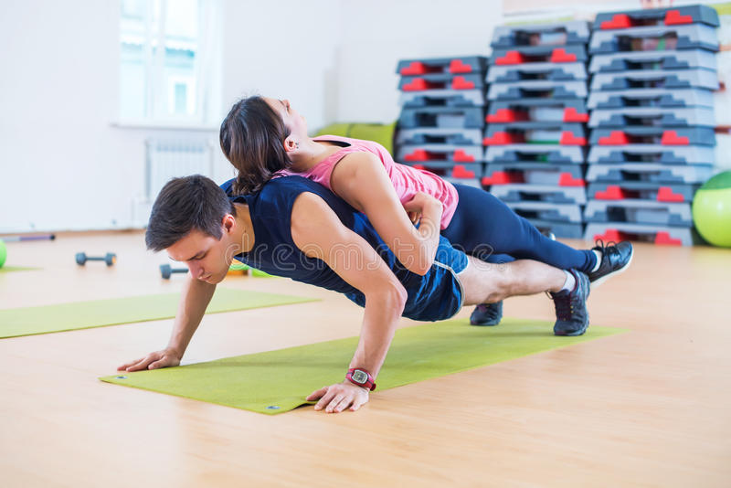 Fit man doing push-ups with woman on back in gym using own weight. Sport training arms, teamwork. royalty free stock photos