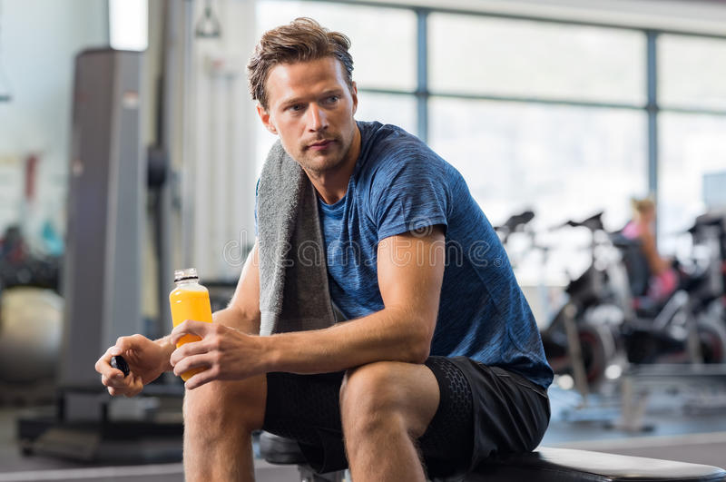 Fit man with energy drink. Handsome young man in sportswear holding bottle of fresh orange juice while resting at gym.Thoughtful fit man sitting alone holding a stock image
