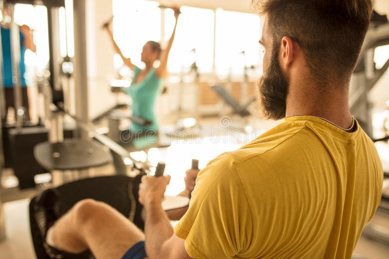 Fit man exercising at the gym on a machine stock image