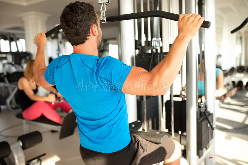 Fit man exercising at the gym on a machine royalty free stock photos