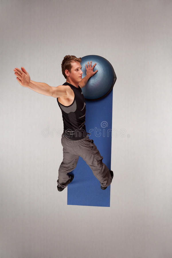 Fit man exercising with half-ball