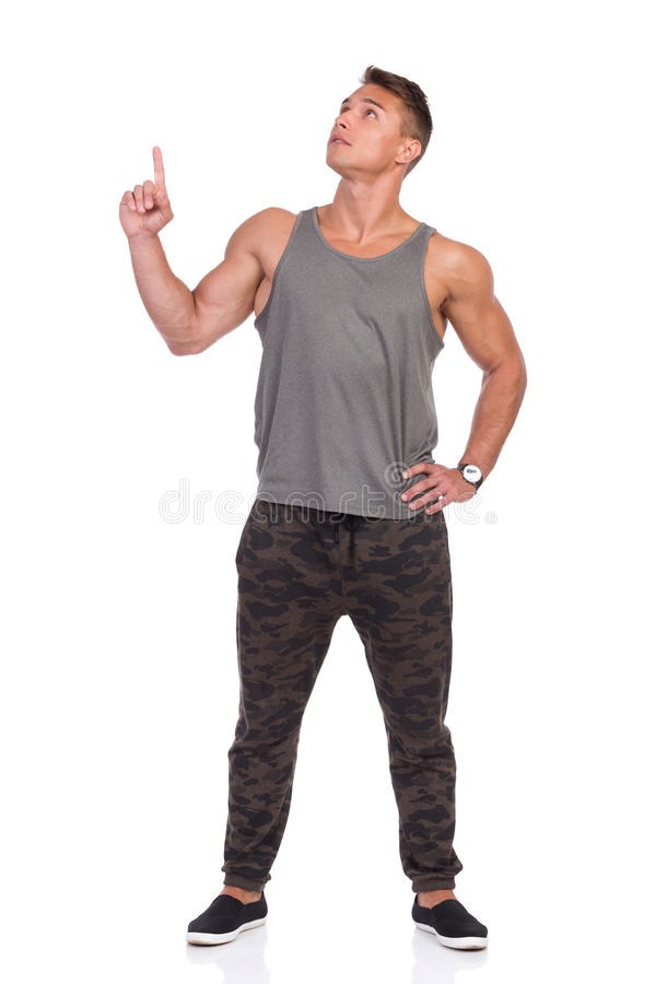 Fit Man In Gray Tank Top And Camo Pants Looking Up And Pointing. Handsome muscular man in pants with camo, gray tank top and black sneakers standing with legs royalty free stock image