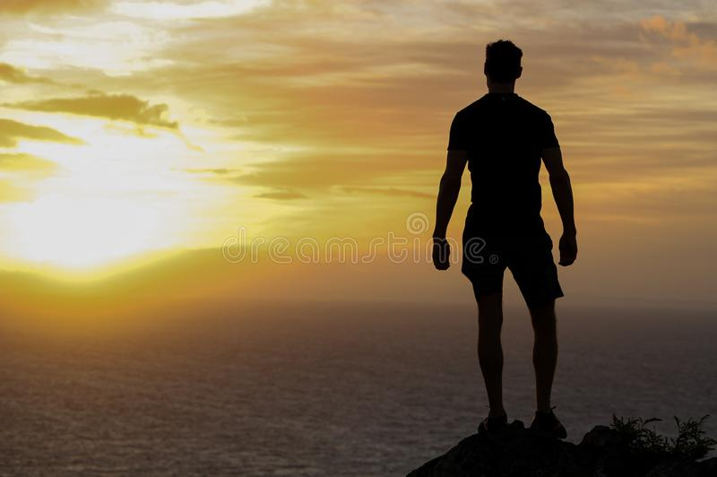 Fit man looking into the sun stock photography