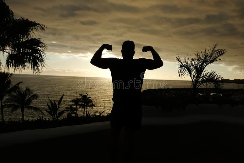 Fit man posing silhouette with sunset over the ocean stock photos