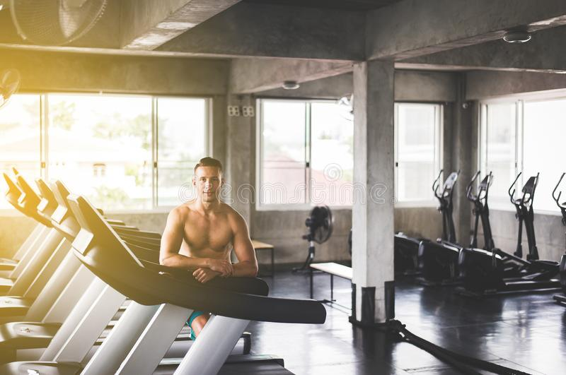 Fit man standing and smiling relax after the training session in gym,Concept healthy and lifestyle,Male taking a break after exerc stock photography