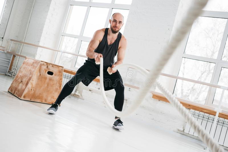 Fit man working out with battle ropes at hall stock photos