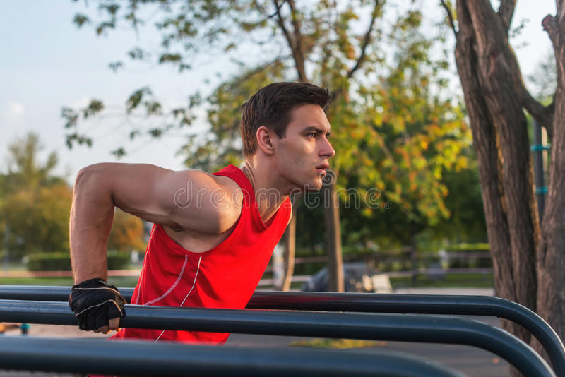 Fit man workout out arms on dips horizontal bars training triceps and biceps doing push ups outdoors. royalty free stock photo