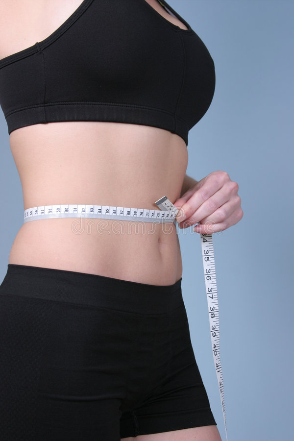 Fit - measuring waist with metric royalty free stock photo