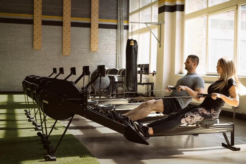 Man and woman training on rowing machines in gym together. Fit men and fit women training on rowing machines in gym together royalty free stock photos