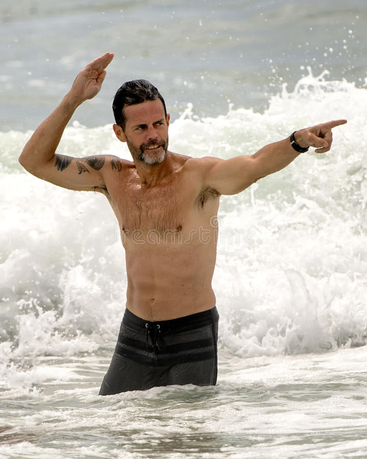 Fit middle-aged man standing in the ocean. A fit middle-aged man is standing in the ocean with a crashing wave in the background. He is pointing forward and stock photos