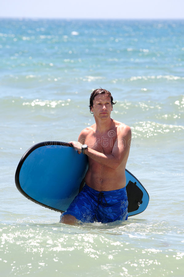 Fit middle aged man surfing on beach in summer stock image