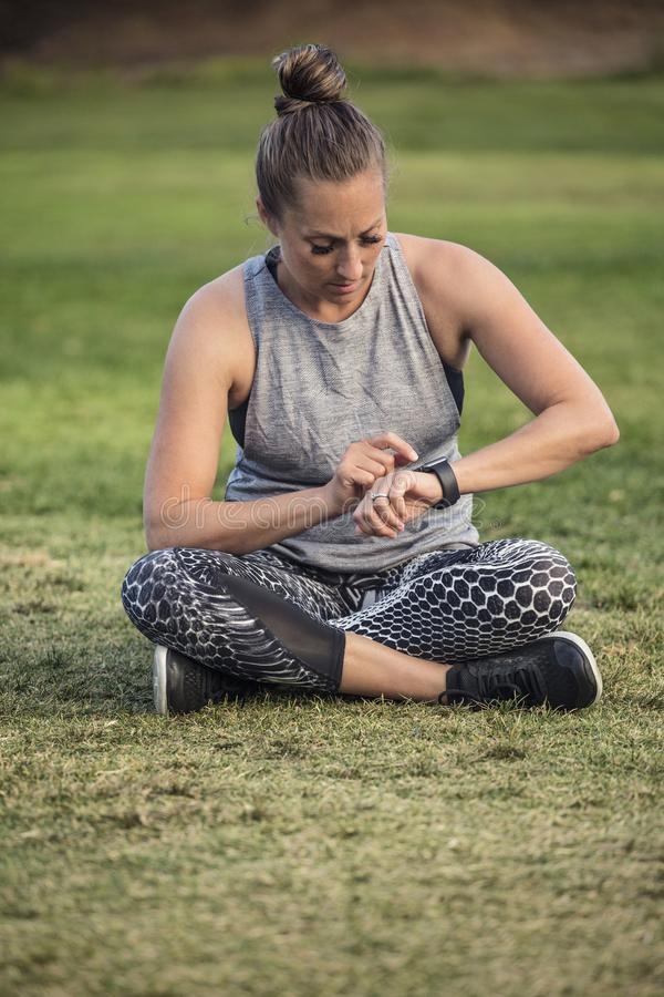 Fit middle aged woman checking her watch after a workout. A beautiful fit middle aged woman checking her watch before or after a workout outdoors. Sitting on the royalty free stock image