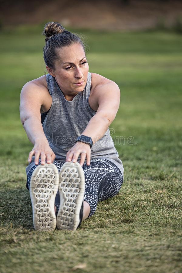 Fit middle aged woman stretching and breathing after a workout. A beautiful fit middle aged woman stretching and breathing after a workout outdoors. Sitting on royalty free stock photos
