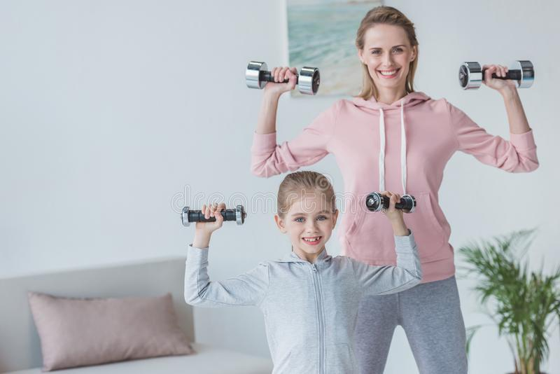 fit mother and daughter working out with dumbbells stock photo