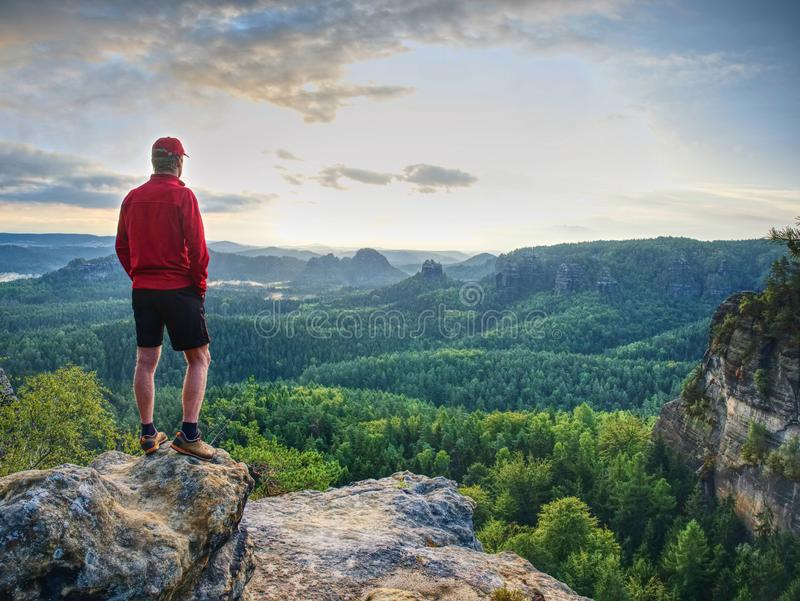 Fit mountain climber or hiker on a rocky summit looking down. Onto forest in a green valley against Sun at horizon stock photos