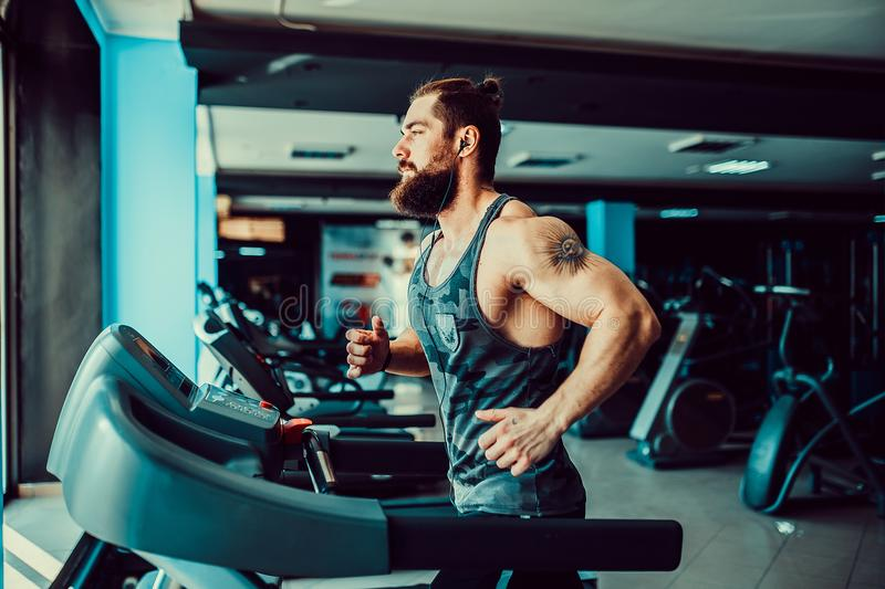 Muscle man running on treadmill. Fit Muscle Bearded Man With Headphones Running on Treadmill in Gym royalty free stock image