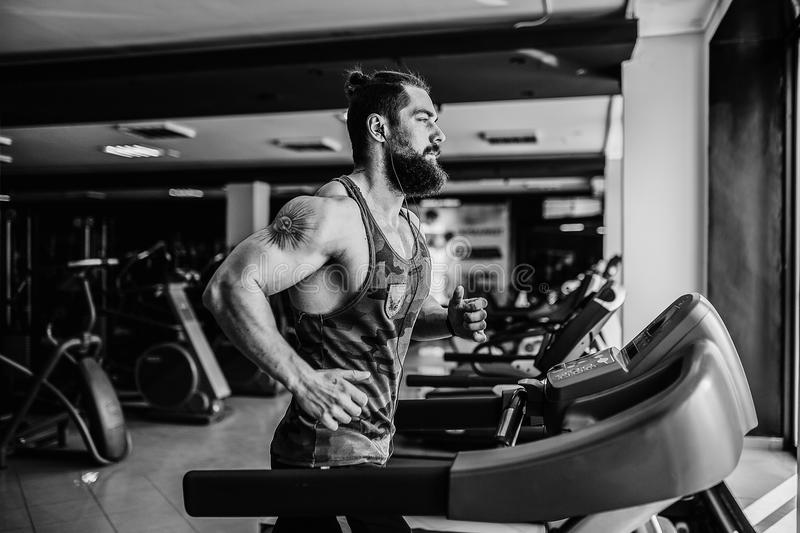 Muscle man running on treadmill. Fit Muscle Bearded Man With Headphones Running on Treadmill in Gym royalty free stock photography