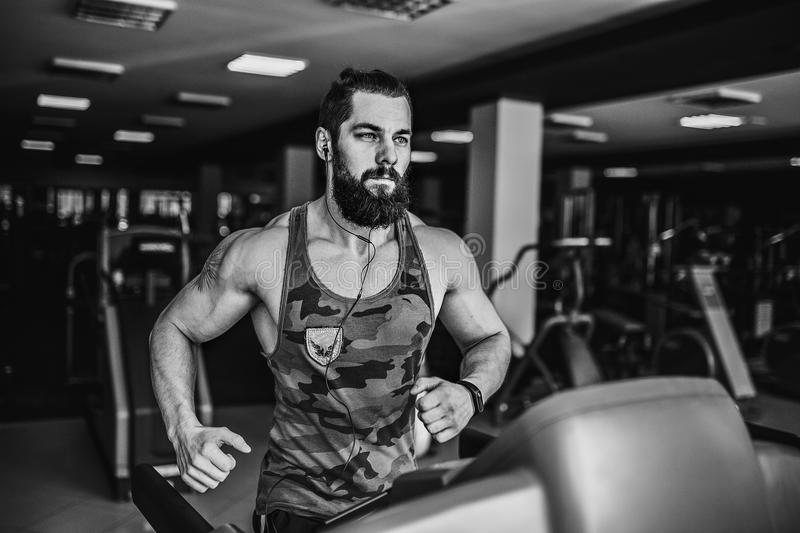 Muscle man running on treadmill. Fit Muscle Bearded Man With Headphones Running on Treadmill in Gym stock photos