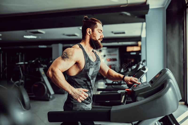 Muscle man running on treadmill. Fit Muscle Bearded Man With Headphones Running on Treadmill in Gym royalty free stock photo