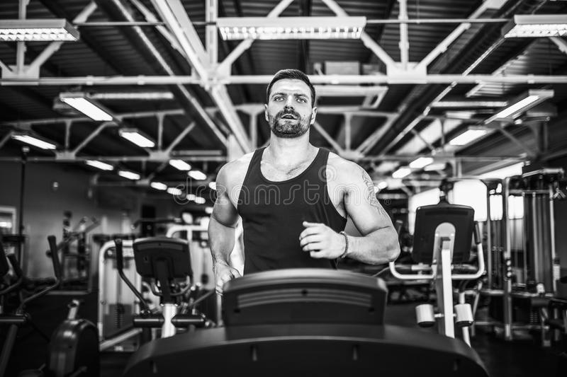 Muscle man running on treadmill. Fit Muscle Man Running on Treadmill in Gym stock image
