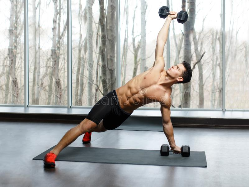 Fit, muscular, athletic young man shirtless in sportswear doing strength exercise with dumbbells in gym. royalty free stock photography