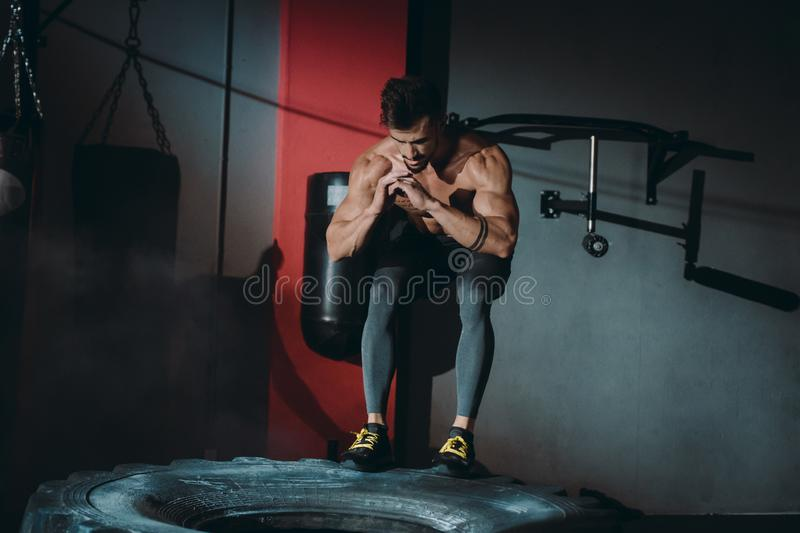 Fit muscular man doing cross fit exercises doing push ups over the a large rubber tyre in a gym class he get sweeting. Fit muscular man doing cross fit exercises stock photos