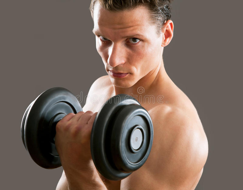 Fit muscular man. Exercising with dumbbell on gray background royalty free stock images