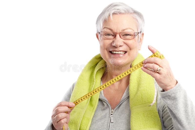 Fit old lady with tape measure smiling. Fit old lady holding tape measure after workout, smiling stock image
