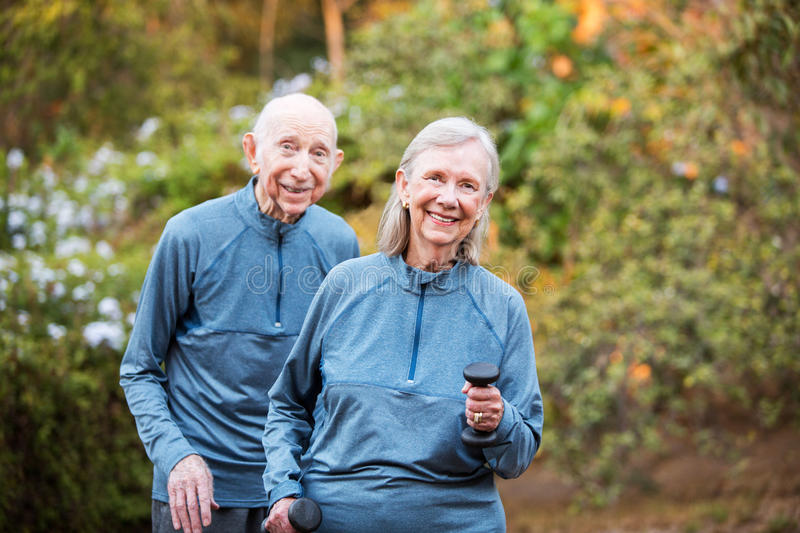 Fit older couple standing in garden stock photography