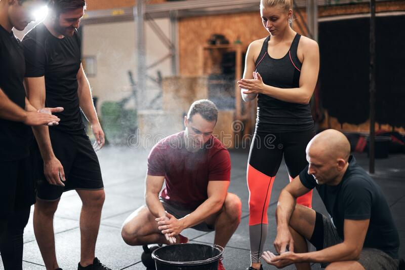 Fit people chalking their hands before a gym workout stock images
