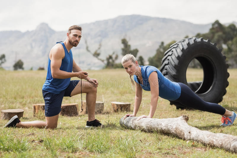 Fit performing pushup exercise while man measuring time royalty free stock photography